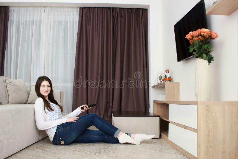 Młoda kobieta ogląda tv na kanapie w żywym izbowym używa pilot do tv fotografia royalty free