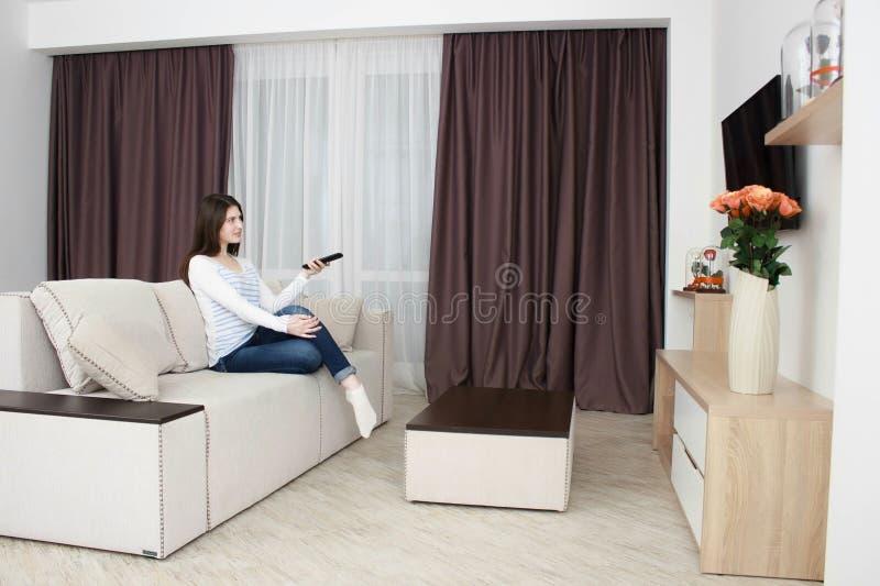 Młoda kobieta ogląda tv na kanapie w żywym izbowym używa pilot do tv zdjęcia royalty free