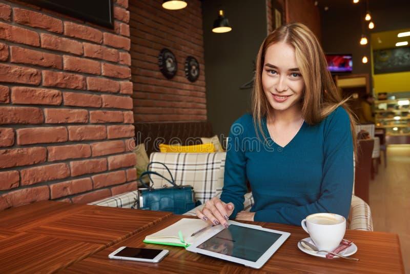 Młoda kobieta ogląda wideo na cyfrowej pastylce podczas odpoczynku w nowożytnym sklep z kawą zdjęcie stock