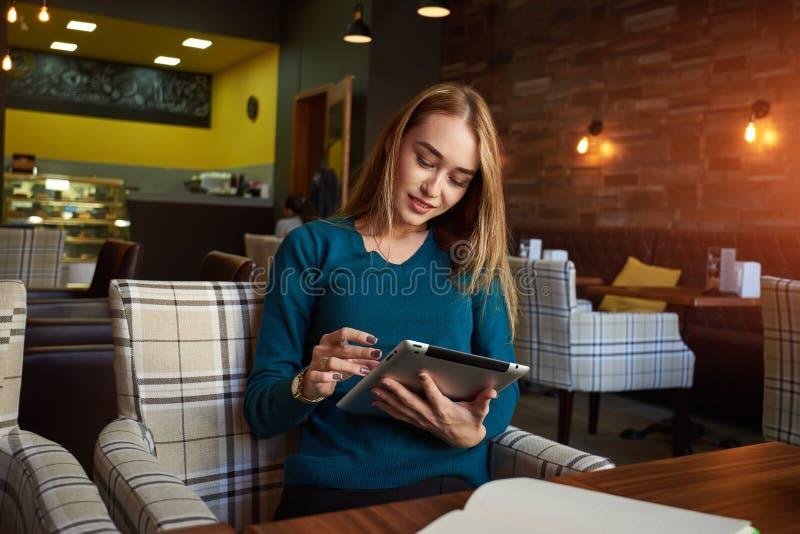 Młoda kobieta ogląda wideo na cyfrowej pastylce podczas odpoczynku w nowożytnym sklep z kawą zdjęcia royalty free