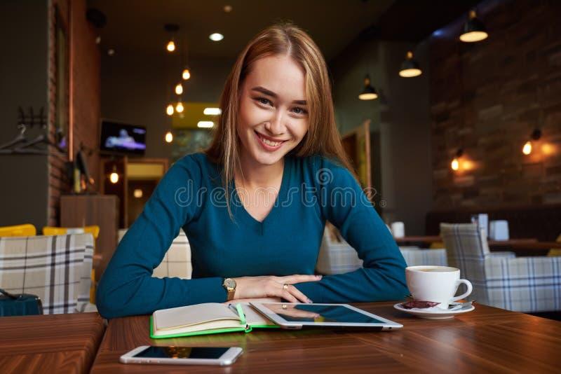 Młoda kobieta ogląda wideo na cyfrowej pastylce podczas odpoczynku w nowożytnym sklep z kawą zdjęcie royalty free