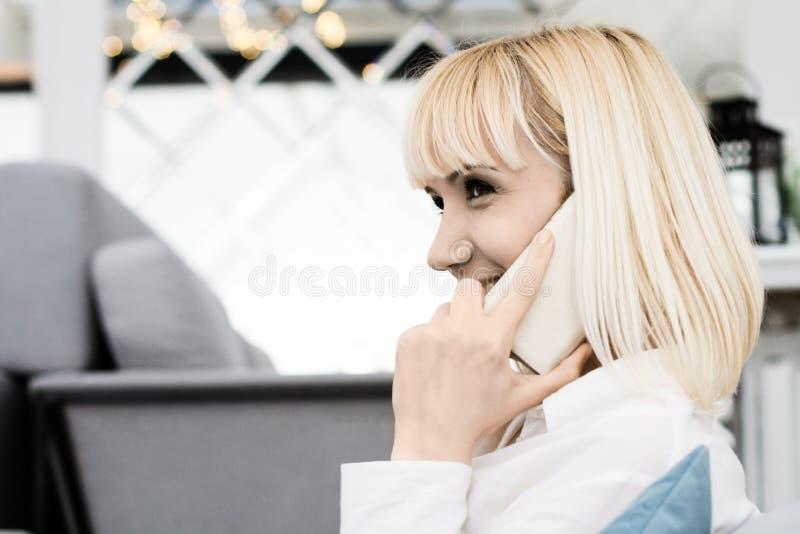 Młoda kobieta ono uśmiecha się i opowiada na telefonie komórkowym obraz royalty free