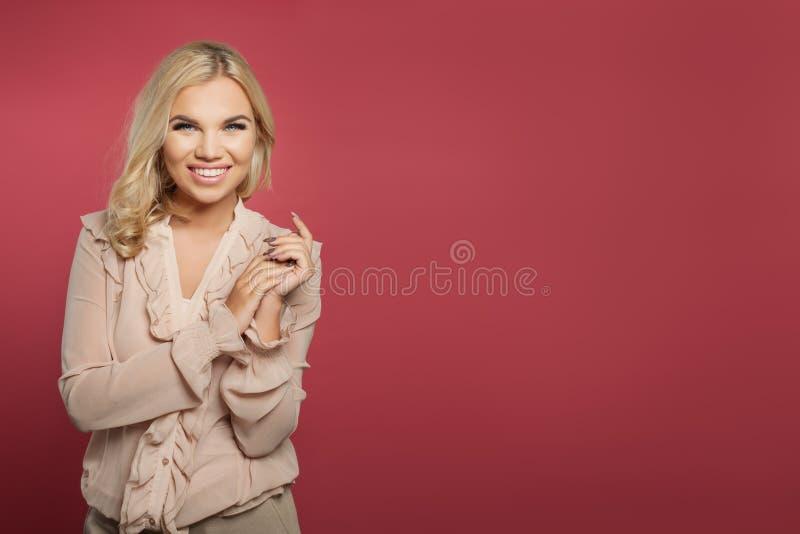 Młoda kobieta ono uśmiecha się na różowym tle Śliczna dziewczyna z blondynka włosy portretem zdjęcia stock