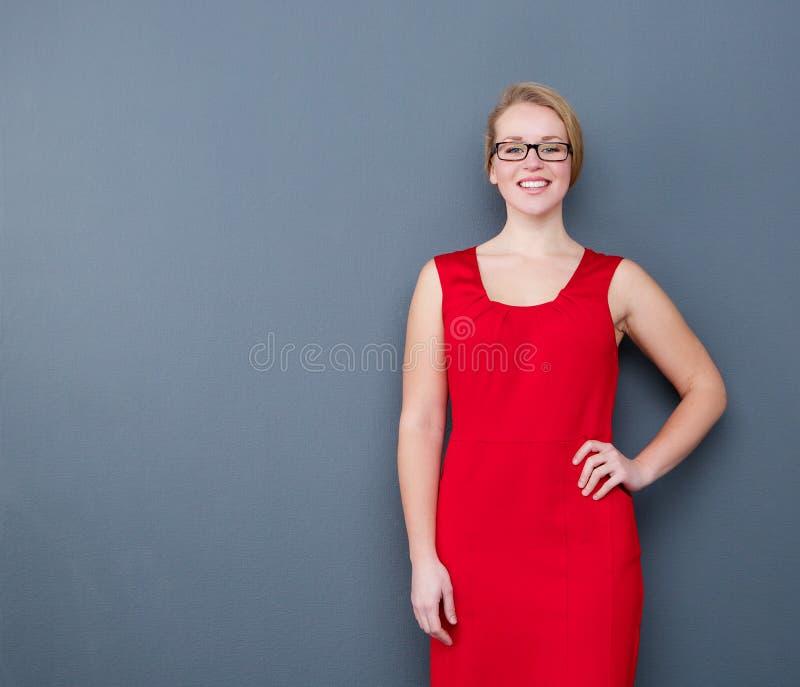 Młoda kobieta ono uśmiecha się w czerwieni sukni fotografia stock