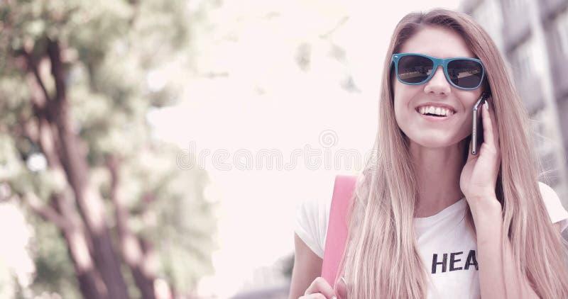 Młoda Kobieta ono Uśmiecha się w Modnym stroju podczas gdy na telefonie obraz stock