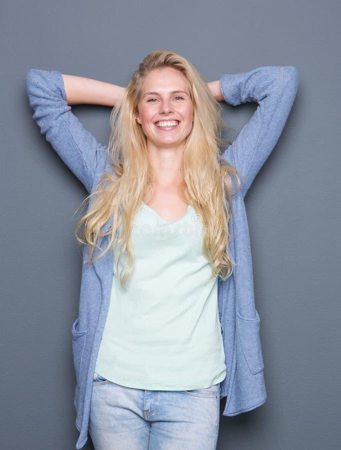 Młoda kobieta ono uśmiecha się z rękami za głową zdjęcie stock