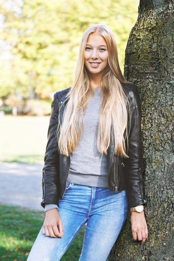 Młoda kobieta opiera przeciw drzewu w parku obraz royalty free