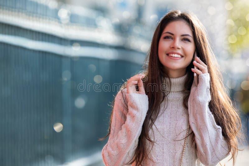 Młoda kobieta opowiada na jej telefonie komórkowym w mieście obraz royalty free