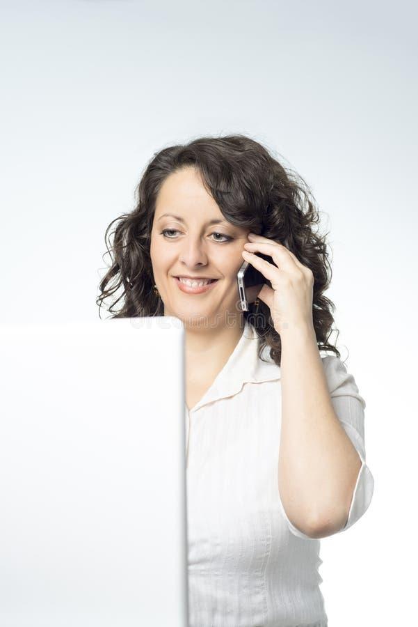 Młoda kobieta opowiada na telefonie przed laptopem obrazy stock