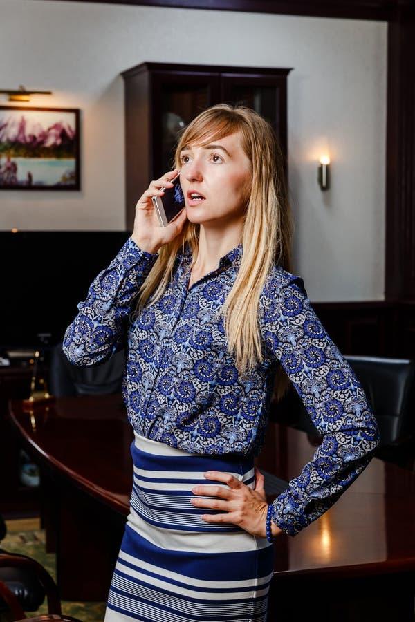 Młoda kobieta opowiada na telefonie w biurze fotografia stock