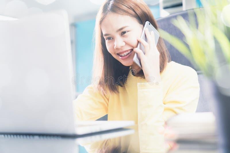 Młoda kobieta opowiada na telefonie w nowożytnym biurze, i radzi klienta obrazy royalty free