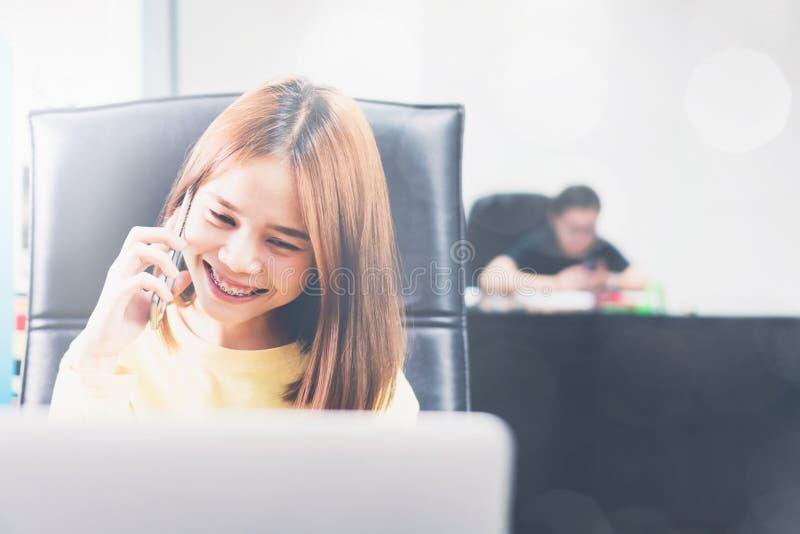 Młoda kobieta opowiada na telefonie w nowożytnym biurze, i radzi klienta zdjęcie stock