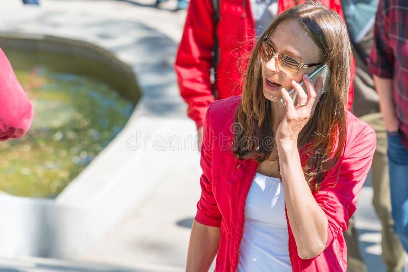 Młoda kobieta opowiada na telefonie w okularach przeciwsłonecznych zdjęcia royalty free