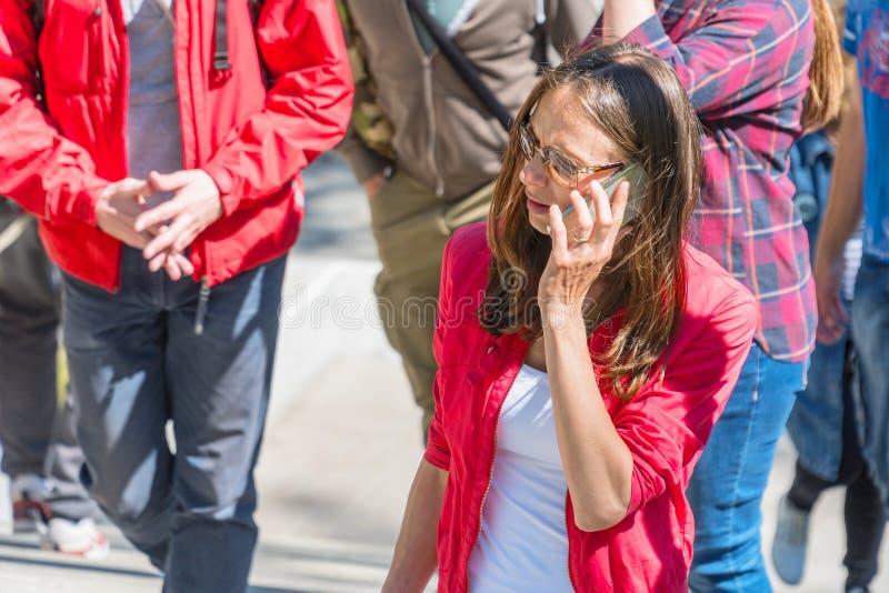 Młoda kobieta opowiada na telefonie w okularach przeciwsłonecznych obraz stock