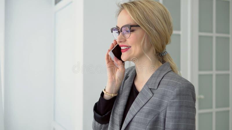 Młoda kobieta opowiada na telefonu ono uśmiecha się w szarej kurtce obraz royalty free