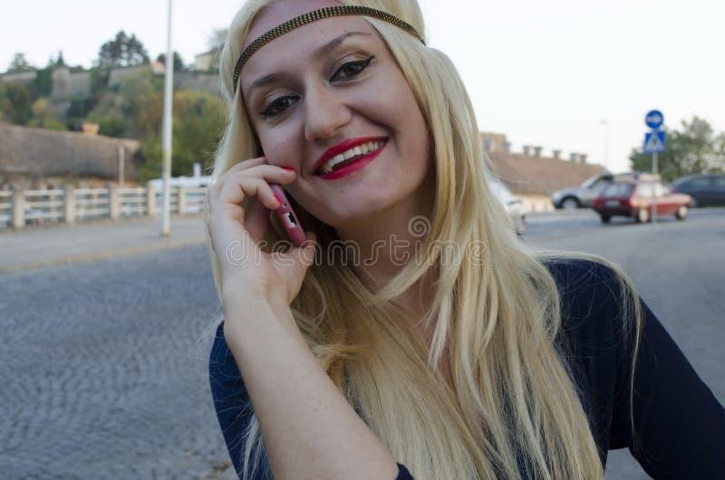 Młoda kobieta opowiada z telefonem komórkowym obrazy stock