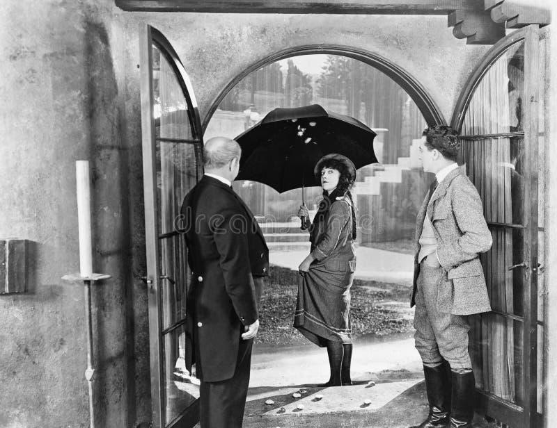 Młoda kobieta opuszcza dom z parasolem spacer w deszczu (Wszystkie persons przedstawiający no są długiego utrzymania i żadny nier fotografia royalty free
