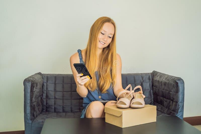Młoda kobieta otrzymywający online zakupy drobnicowy otwarcie i kupienie mody rzeczy boksujemy używać kartę kredytową fotografia royalty free