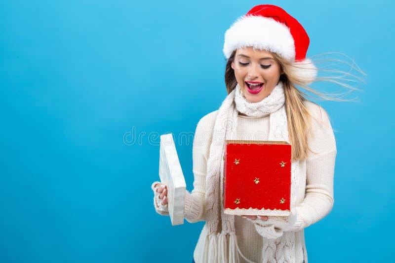 Młoda kobieta otwiera Bożenarodzeniowego prezenta pudełko fotografia royalty free