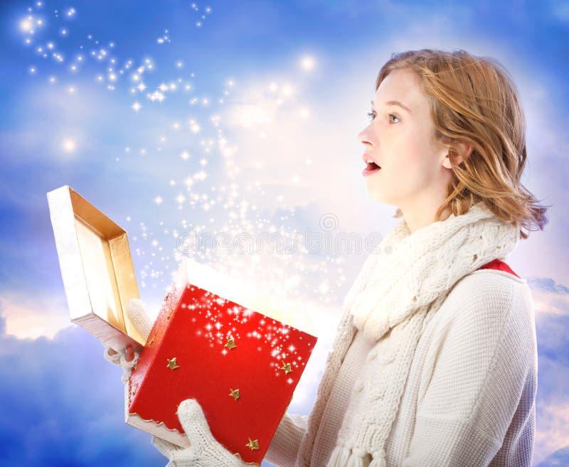 Młoda kobieta otwiera magicznego Bożenarodzeniowego prezent obrazy royalty free