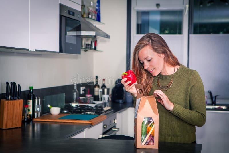 Młoda kobieta otwiera pakunek świezi składniki dla zdrowego gościa restauracji zdjęcia royalty free