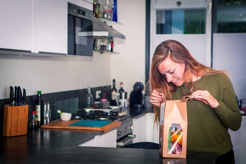 Młoda kobieta otwiera pakunek świezi składniki dla zdrowego gościa restauracji zdjęcie stock