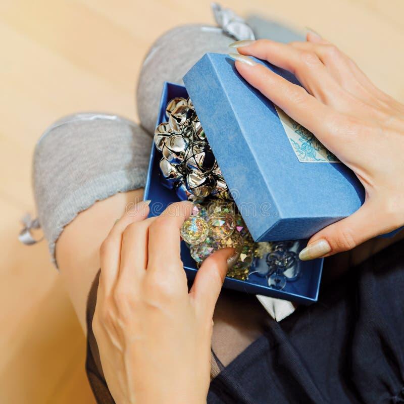 Młoda kobieta otwiera prezenta pudełko z biżuterii rzeczą obraz royalty free