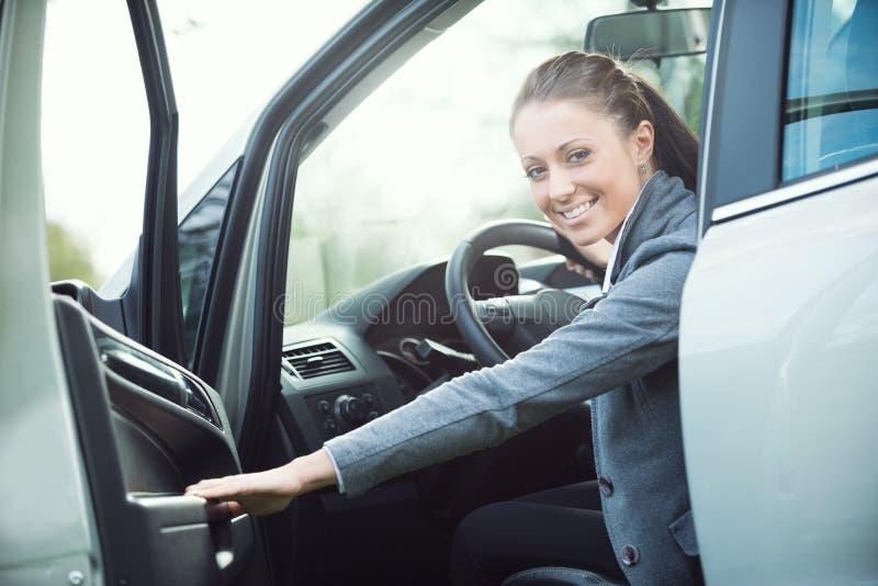 Młoda kobieta otwiera samochodowego drzwi obraz stock
