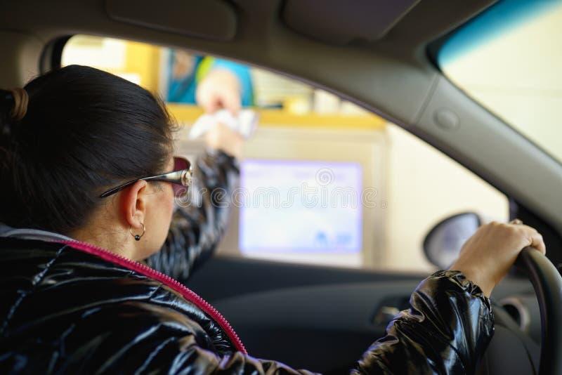 Młoda kobieta płaci opłatę drogowa na autostradzie przy tollbooth obrazy stock