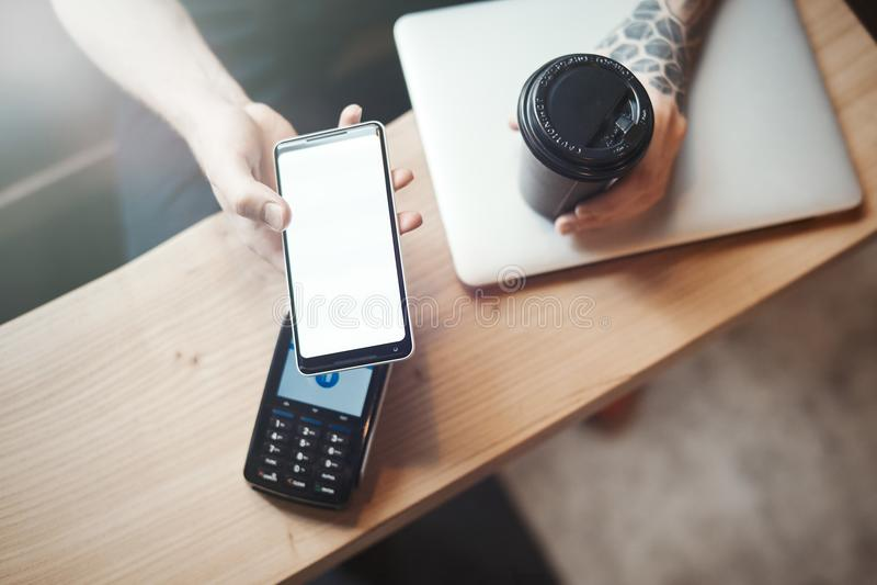 Młoda kobieta płaci przez płatniczego terminal i telefonu komórkowego w kawiarni obrazy royalty free