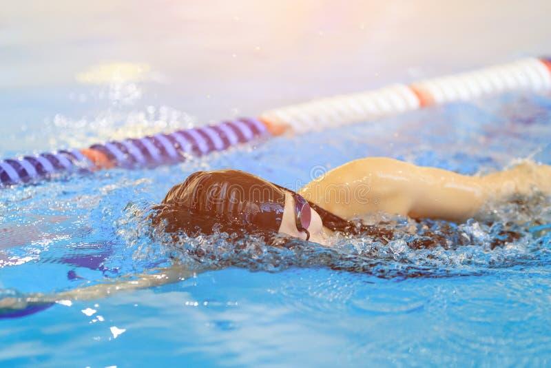 Młoda kobieta pływa frontowego kraula uderzenia styl w błękitne wody salowym biegowym basenie w gogle i nakrętka obrazy royalty free