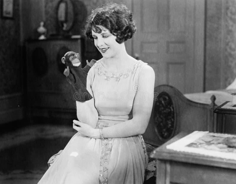 Młoda kobieta patrzeje małpiej ręki kukły i ono uśmiecha się (Wszystkie persons przedstawiający no są długiego utrzymania i żadny fotografia stock
