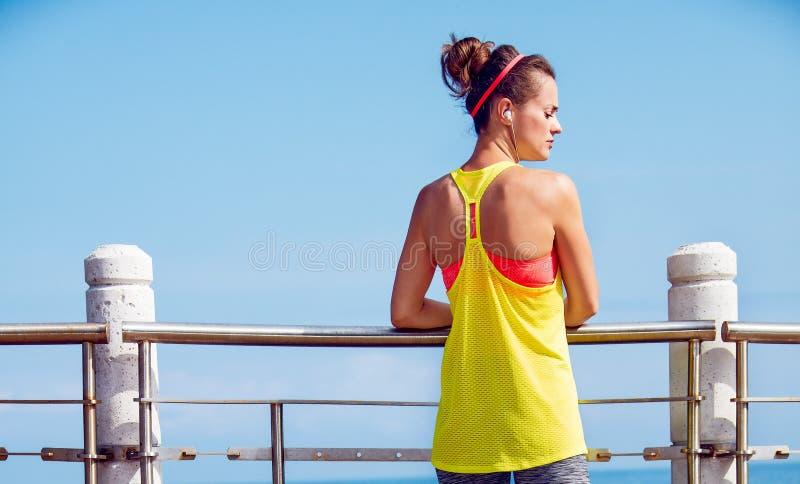 Młoda kobieta patrzeje na boku przy bulwarem w sprawność fizyczna stroju fotografia stock