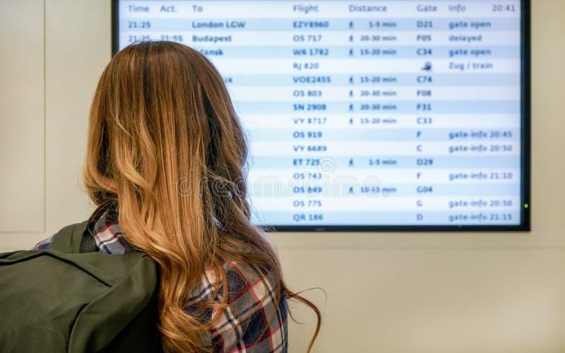 M?oda kobieta patrzeje odjazd deski ekran przy lotniskiem z zielonym plecakiem, widok od za zdjęcia stock