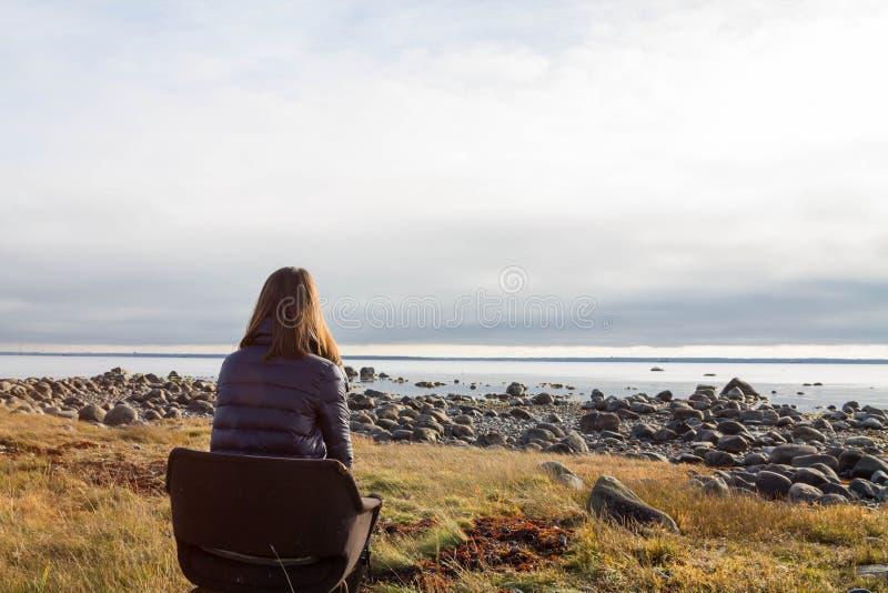 Młoda kobieta patrzeje skalistą plażę siedzi samotnie w krześle zdjęcia royalty free