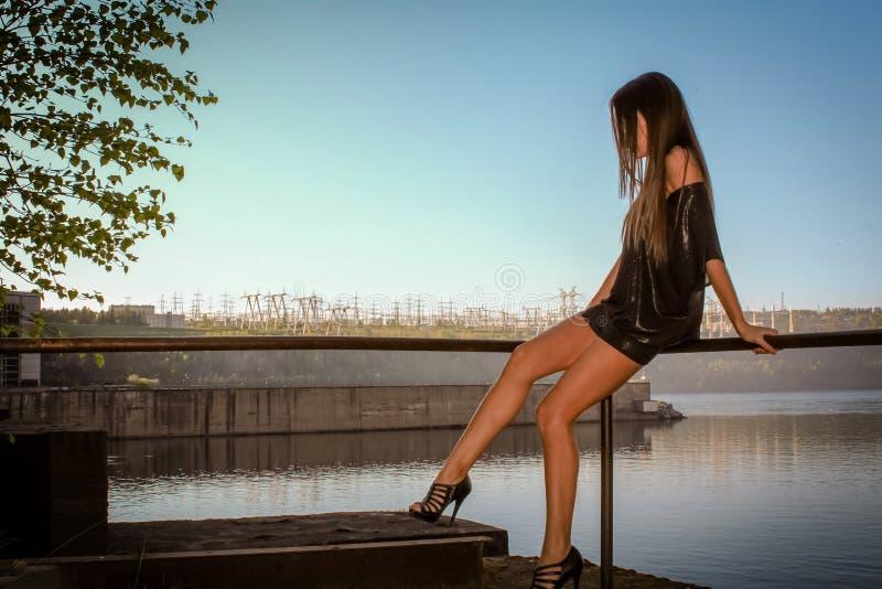 Młoda kobieta patrzeje zmierzch w ślicznym lato sukni obsiadaniu na molu obraz stock