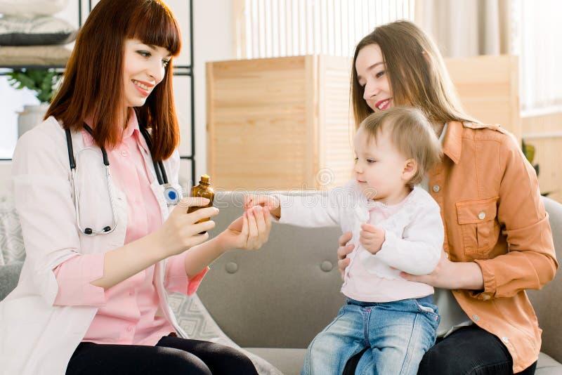 Młoda kobieta pediatra przepisuje medycynę i daje chora dziewczynka, siedzi z jej matką zdjęcie royalty free