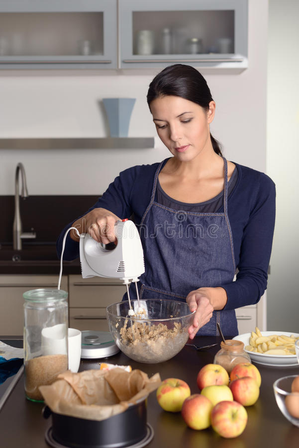 Młoda kobieta piec jabłczanego kulebiaka w kuchni zdjęcia royalty free