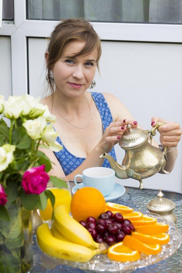 Młoda kobieta pije herbaty outdoors fotografia stock