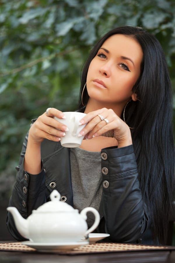 Młoda kobieta pije herbaty przy chodniczek kawiarnią obrazy stock
