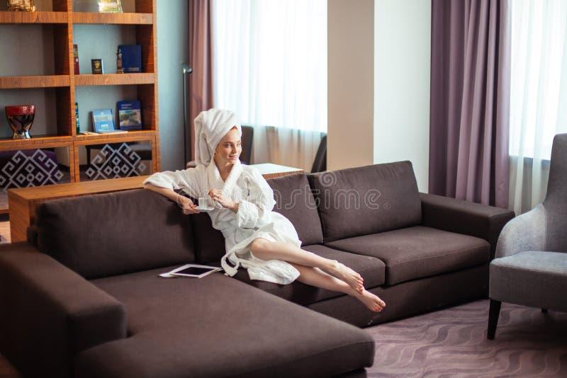 Młoda kobieta pije kawę i czytanie na cyfrowej pastylce w bathrobe zdjęcia royalty free