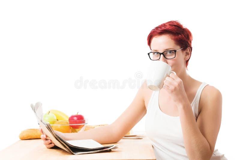 Młoda kobieta pije kawową czytelniczą gazetę zdjęcie stock