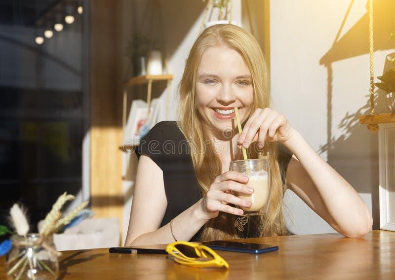 Młoda kobieta pije kawowych siedzących salowych uśmiechy duży uśmiech w miastowej kawiarni Cukierniany miasto styl ?ycia Przypadk zdjęcia stock