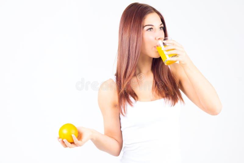 Młoda kobieta pije sok pomarańczowego i trzyma pomarańczowy w jej ręce Zdrowy Styl życia obrazy stock