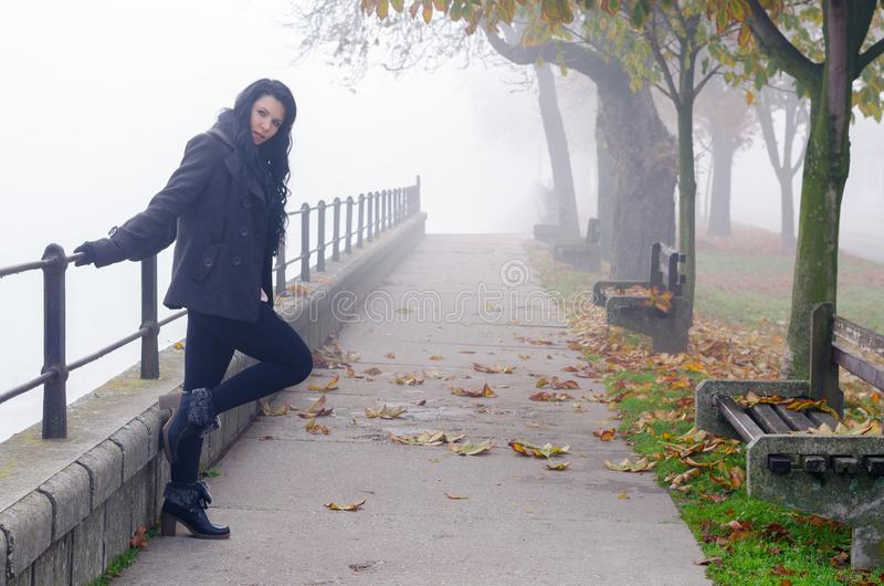 Młoda kobieta plenerowa na mglistym jesień dniu zdjęcie stock