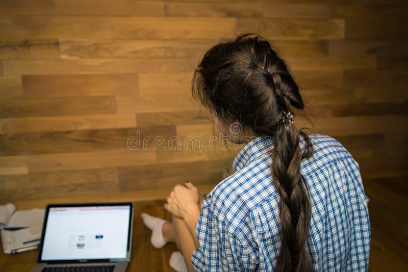 Młoda kobieta po pracującego dnia siedzi na podłoga biurze w domu zdjęcia royalty free
