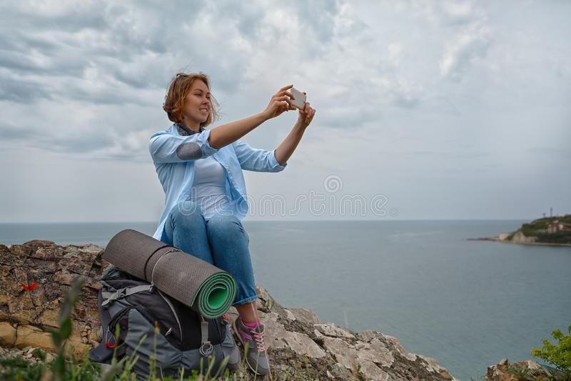Młoda kobieta podbijał halnego wierzchołek i decydował brać obrazek piękny panoramiczny widok zdjęcie stock