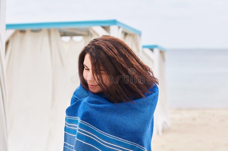 Młoda kobieta podczas camping podróży wycieczki stojaków na plaży tulonej w rzut koc szkockiej kracie lub inspirującej i marzycie obraz stock