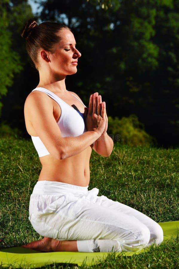 Młoda kobieta podczas joga medytaci w parku fotografia stock