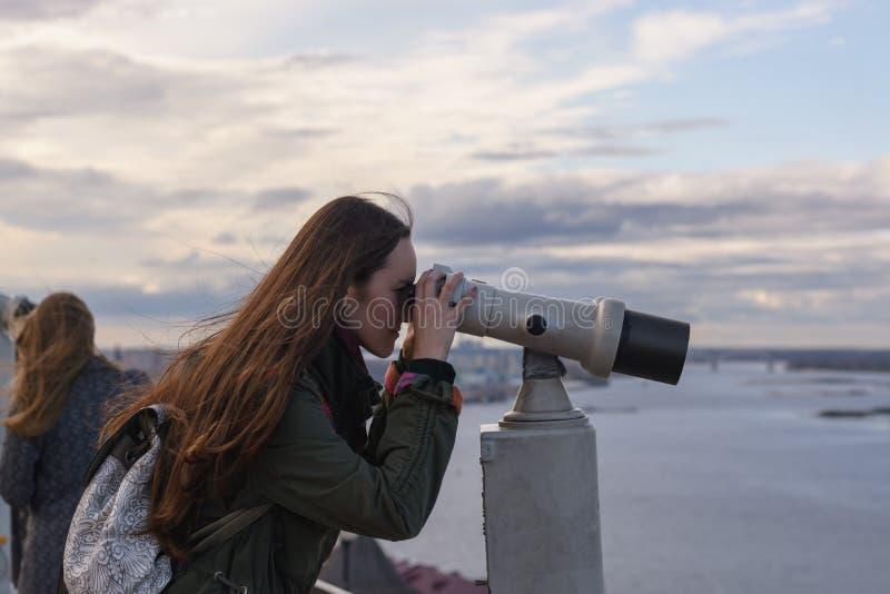 Młoda kobieta podróżnik patrzeje przez lornetek przy panoramą miasto Nizhny Novgorod na obserwacja pokładzie zdjęcia royalty free